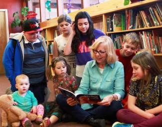 Author Lisa Boulton reads a book with children surrounding her.
